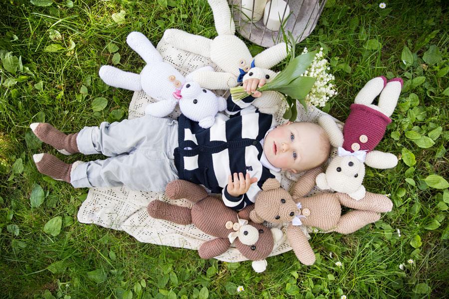 Kūdikis tarp nertų žaislų meškiukų fotosesijos dekoravimas