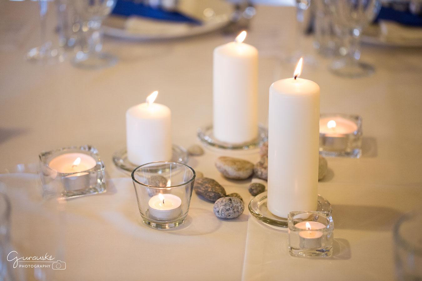 Stalo dekoravimas balta žvakė akmenukai