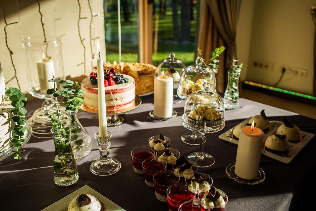 Storos baltos žvakės ir stiklinėmis žvakidėmis dekoruotas saldus stalas